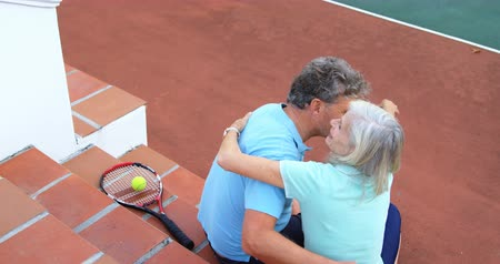 tennis rackets : Romantic senior couple hugging on tennis court stairs 4k