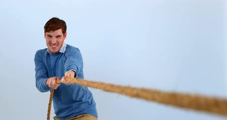 штамм : Man pulling a rope tug of war against blue background 4k Стоковые видеозаписи