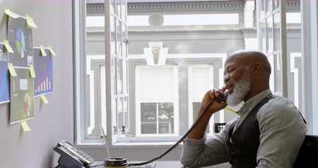 megbeszélés : Businessman talking on landline at desk in office 4k Stock mozgókép