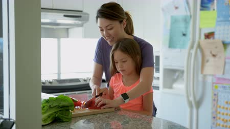 home life : Mother teaching daughter to chop vegetables in kitchen at home 4k