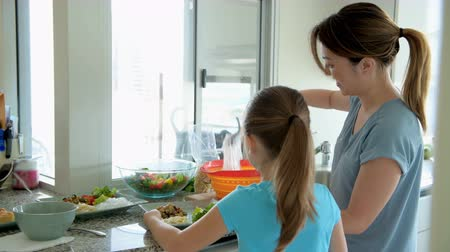 arranging : Woman with her daughter keeping noddle on plate in kitchen at home 4k Stock Footage