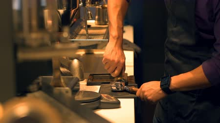 coffee press : Barista pressing ground coffee into portafilter by tamper to making coffee at cafe 4k Stock Footage