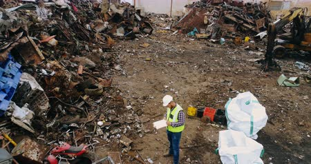 discard : Drone shot of man checking scrap in scrapyard 4k Stock Footage
