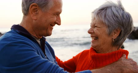 fondness : Senior couple embracing each other in the beach at dusk 4k Stock Footage