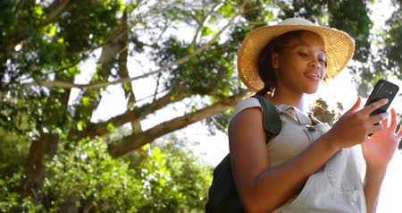 dungarees : Female hiker using mobile phone at countryside on a sunny day 4k Stock Footage