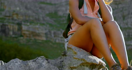 dungarees : Thoughtful female hiker relaxing on rock at countryside 4k