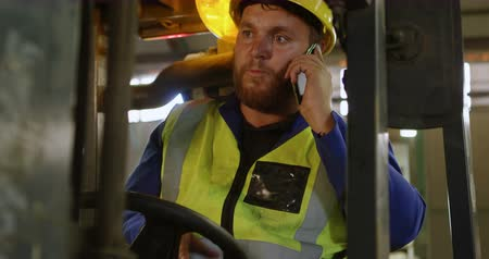 forklift : Male worker talking on mobile phone in warehouse 4k Stock Footage