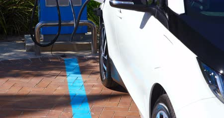 híbrido : Electric car charging at charging station on a sunny day 4k Vídeos