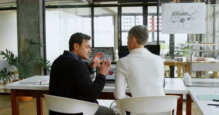 car designer : Car designers discussing to each other at desk in office 4k Stock Footage