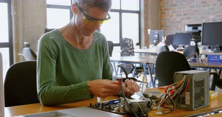 soldering iron : Female electrical engineer soldering a circuit board in office 4k Stock Footage