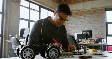 componente : Male electrical engineer soldering a circuit board in office 4k