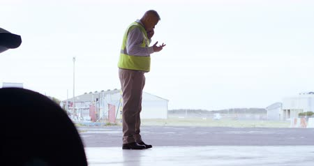 hangar : Male engineer talking on mobile phone in aerospace hangar 4k Stock Footage