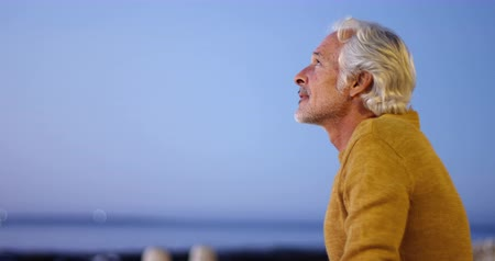 active ageing : Thoughtful senior man sitting outdoors against sky 4k