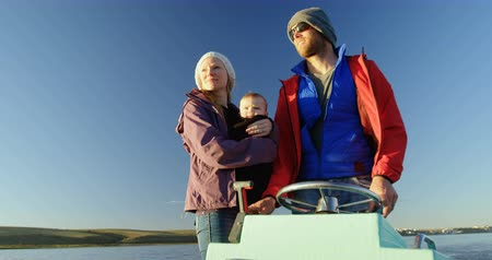 evez : Parents with baby travelling in motorboat on river 4k Stock mozgókép