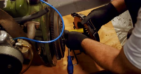 dungarees : High angle view of mechanic servicing mac wheel in garage 4k