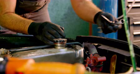 dungarees : Male mechanic servicing a car in garage 4k