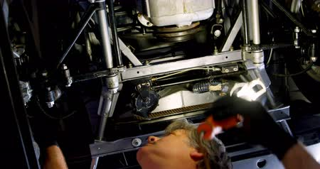 dungarees : Low angle view of male mechanic servicing a car in garage 4k