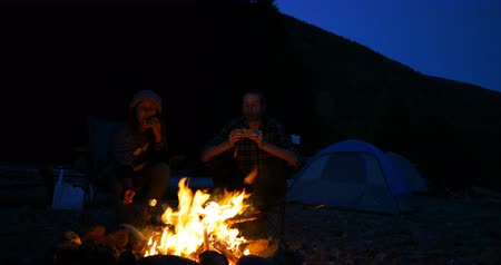 fűtés : Hiker couple eating food near campfire at countryside 4k