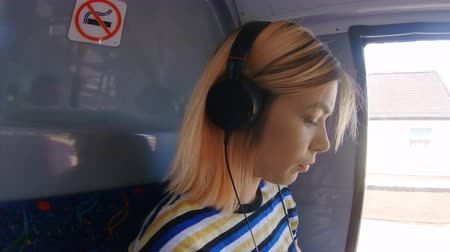 fone de ouvido : Side view of girl listening music on a bus 4k