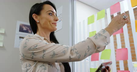 görgetés : Female executive removing sticky note while using digital tablet in office 4k