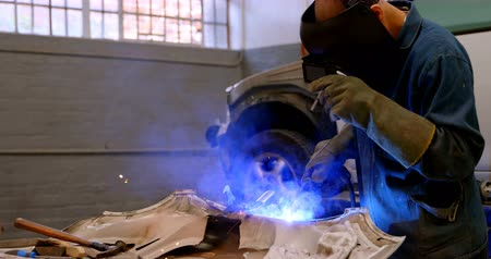 welding torch : Mechanic using wielding torch on a car part in garage 4k
