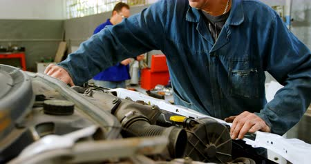 spare part : Mechanic examining a car at repair garage 4k Stock Footage