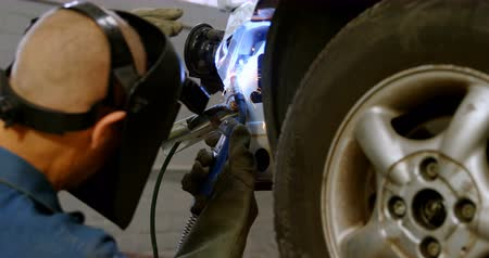 welding torch : Mechanic using wielding torch on a car at repair garage 4k