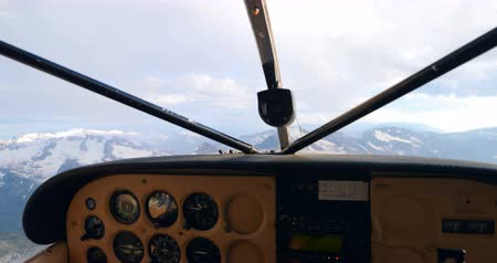 temprature : Head shot of pilot flying aircraft over snowcovered mountain 4k