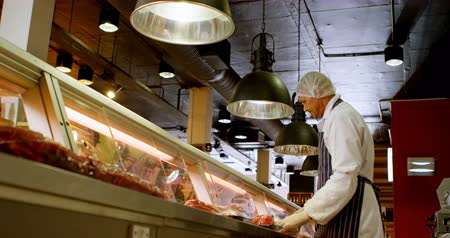 arranging : Butcher arranging wrapped meat in refrigerator at shop 4k Stock Footage