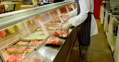 butchers shop : Low section of butcher arranging wrapped meat in refrigerator at shop 4k