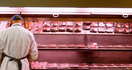 butchers shop : Rear view of butcher arranging wrapped meat in rack at shop 4k Stock Footage