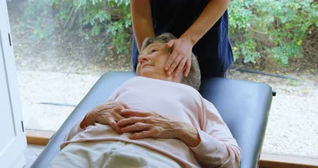 terapeuta : Physiotherapist giving head massage to senior woman in clinic 4k