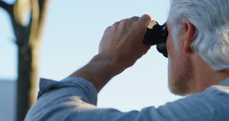 active ageing : Senior man looking through binoculars at countryside on a sunny day 4k Stock Footage
