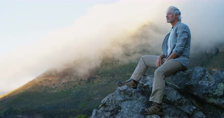 active ageing : Active senior man relaxing on a rock at countryside 4k