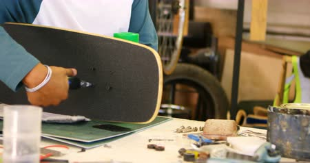 kwaliteit : Mens die skateboard in workshop 4k maakt Stockvideo