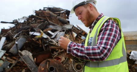 work hard : Male worker writing on clipboard in the junkyard 4k
