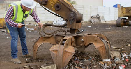 discard : Male worker looking at machine in the junkyard 4k