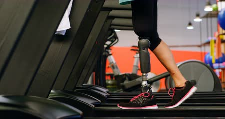 handikap : Low section of senior woman exercising on treadmill in fitness studio 4k Stok Video