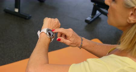 portable information device : High angle view of senior woman checking her smartwatch in fitness studio 4k Stock Footage