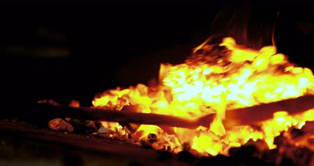 heating up metal : Blacksmith heating metal rod in fire at workshop 4k