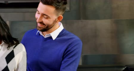 interagindo : Smiling couple talking to each other in office 4k