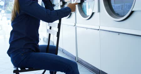 conveniente : Side view of woman using mobile phone at laundromat 4k