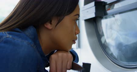 mosás : Thoughtful woman looking at washing machine at laundromat 4k Stock mozgókép