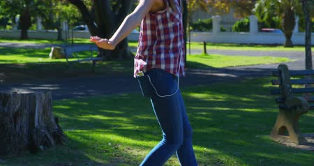 balanceamento : Beautiful woman listening music while playing in the park 4k