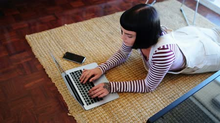 homely : High angle view of woman using laptop on floor at home 4k