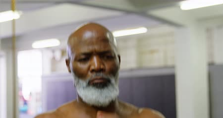rugalmas : Senior man exercising with barbell weight in fitness studio 4k