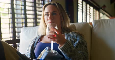 domácké : Woman having red wine while watching television at home 4k