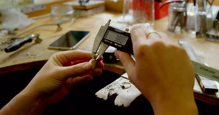 craftswoman : Close-up of jewelry designer using caliper in workshop 4k