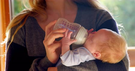 bottle feeding : Mother feeding milk to her baby boy in living room at home 4k