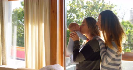 bottle feeding : Lesbian couple holding their baby boy at home 4k